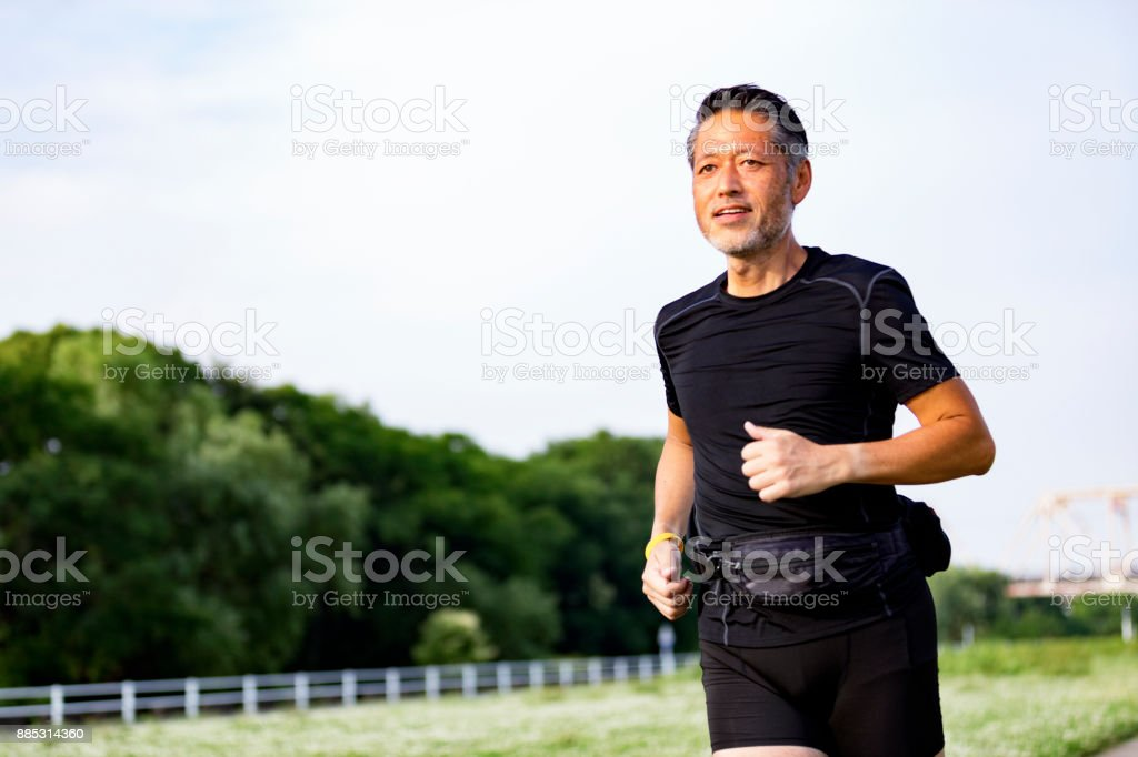 Active Japanese senior man jogging against the sunshine stock photo