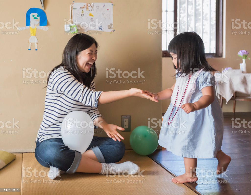Active Japanese Toddler Girl Slapping Hands with Older Sister stock photo