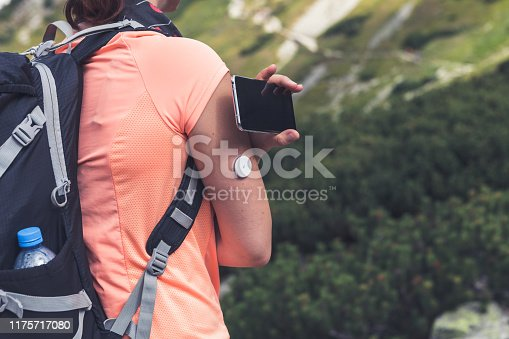 Active life of diabetics, woman hiking and checking glucose level with a remote sensor and mobile phone, sensor checkup glucose levels without blood. Diabetes treatment. Purple toned image.