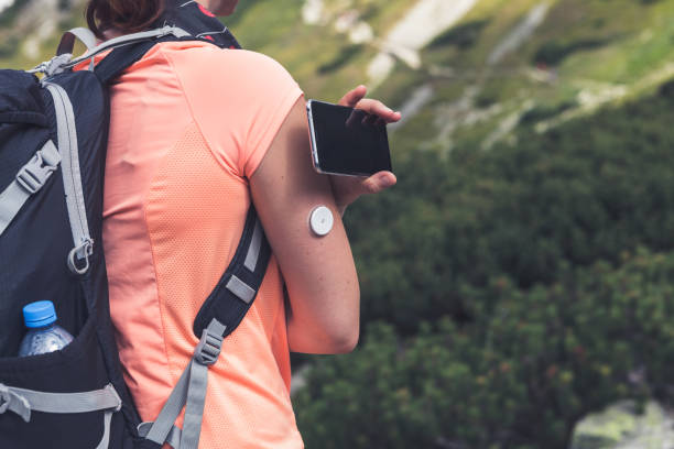 Active life of diabetics, woman hiking and checking glucose level with a remote sensor and mobile phone stock photo