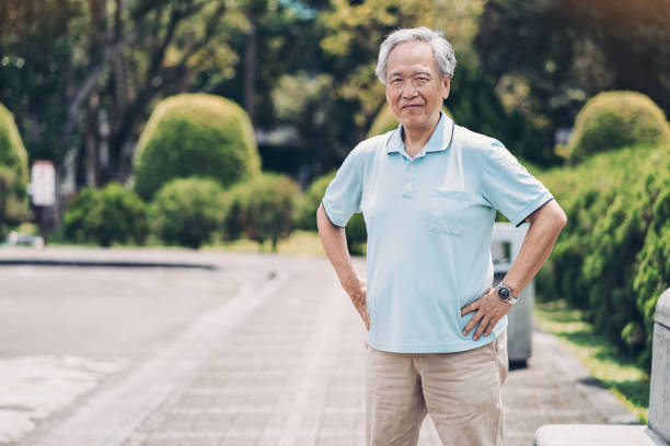 Active lifestyle at senior age Portrait of a senior Chinese ethnicity man in a park akimbo stock pictures, royalty-free photos & images