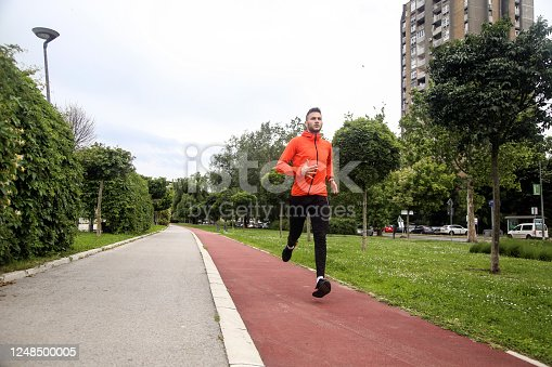 Young man running on a track. About 25 years old, Caucasian male.