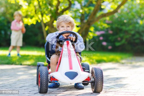 915609494istockphoto Active little boy driving pedal car in summer garden 510391895