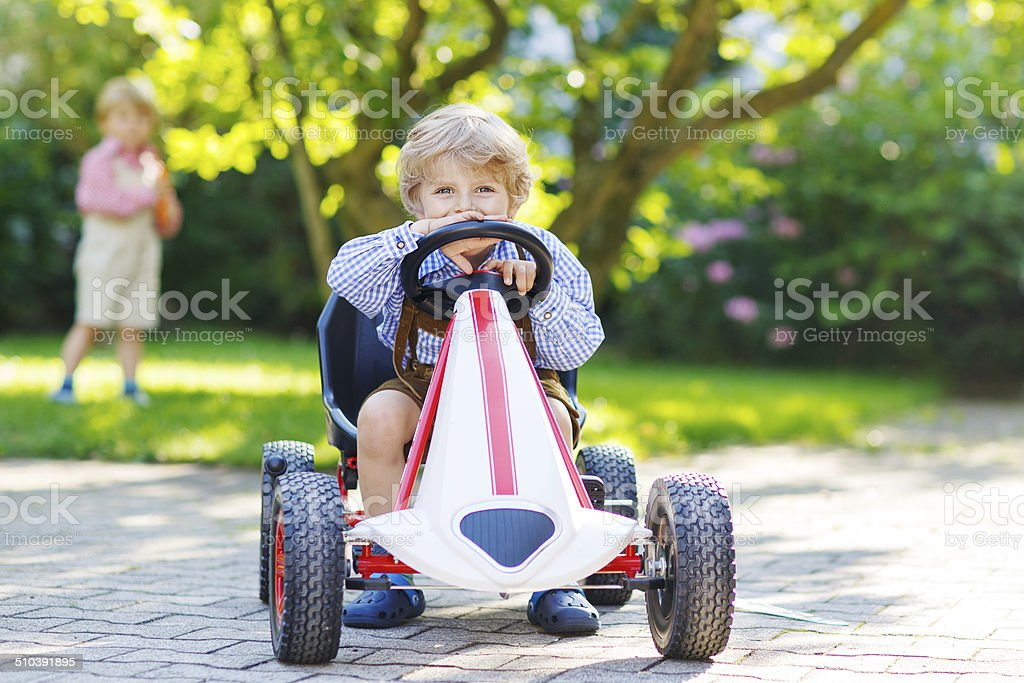 Active little boy driving pedal car in summer garden stock photo