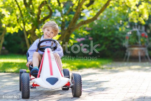 915609494istockphoto Active little boy driving pedal car in summer garden 510391901