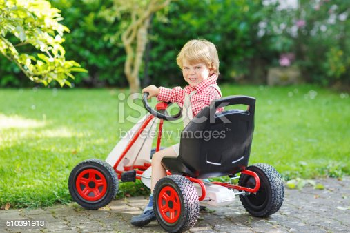 915609494istockphoto Active little boy driving pedal car in summer garden 510391913