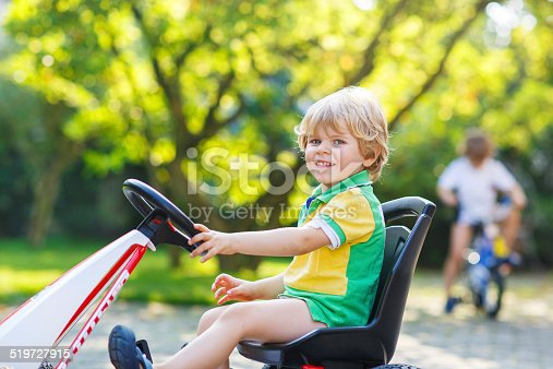 915609494istockphoto Active little boy driving pedal car in summer garden 519727915