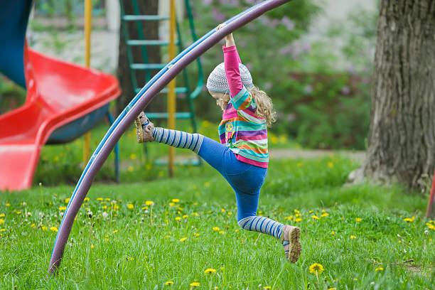 aktive kleines mädchen klettern affe bar im freien auf den spielplatz - horizontal gestreiften vorhängen stock-fotos und bilder