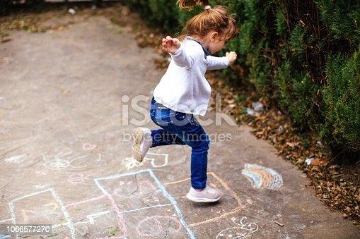 Active little girl enjoying playing hopscotch