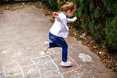 Active little girl enjoying playing hopscotch