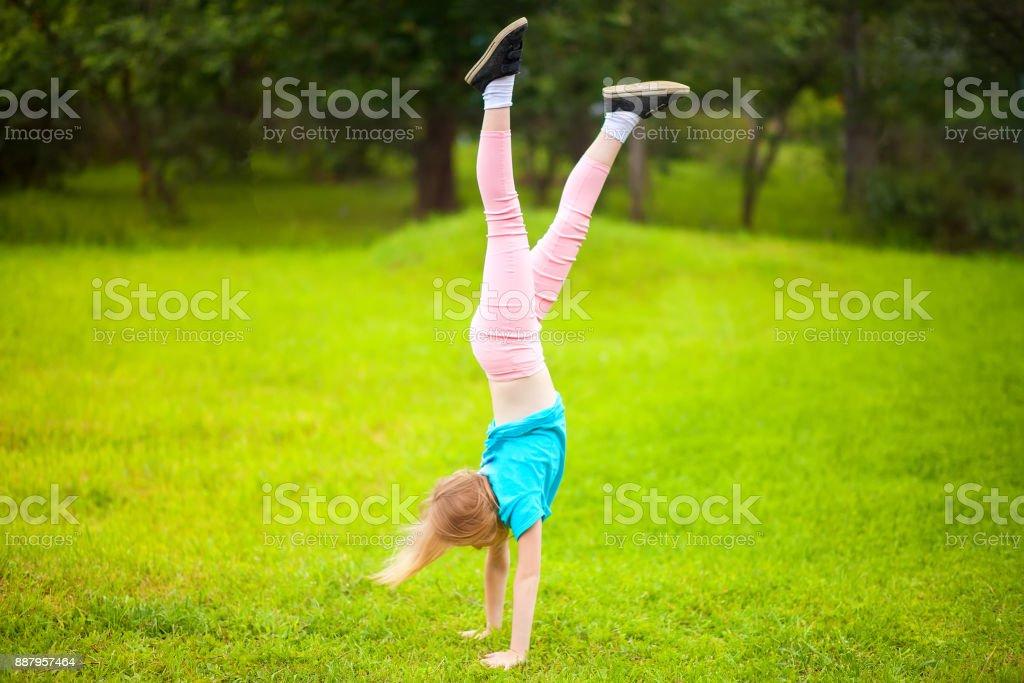Active little school girl somersault outdoors. stock photo