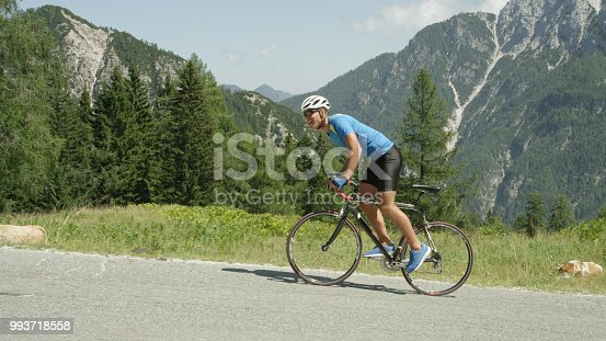 Active male on road bicycle looking towards the approaching finish line of mountain race. Pro road cyclist enduring a difficult ascent on a scorching hot summer afternoon in the breathtaking mountains