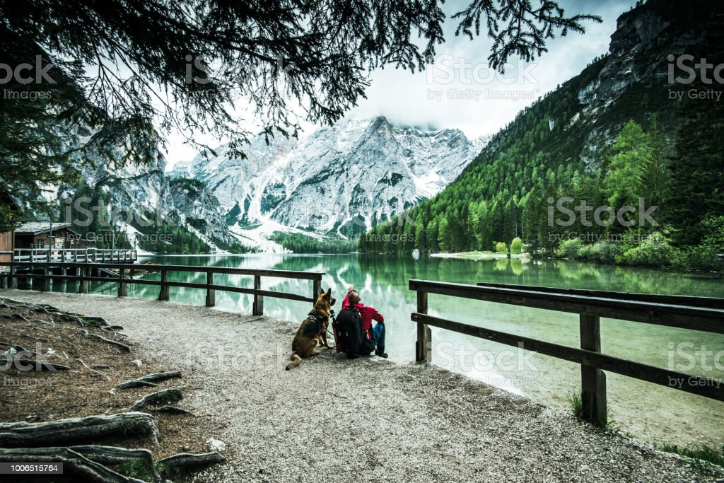 Active man and dog looking at Pragser Wildsee or Braies Lake