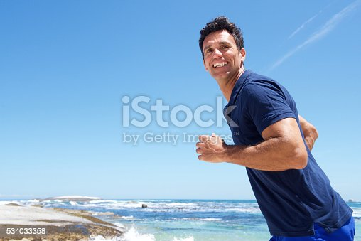 istock Active man casually running at the beach 534033358