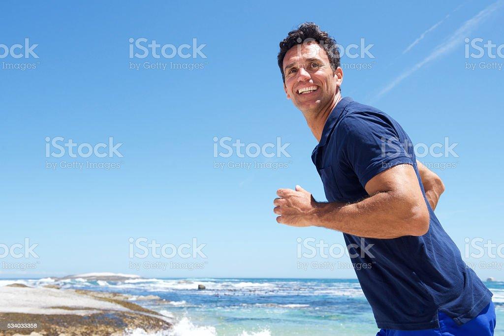 Active man casually running at the beach stock photo