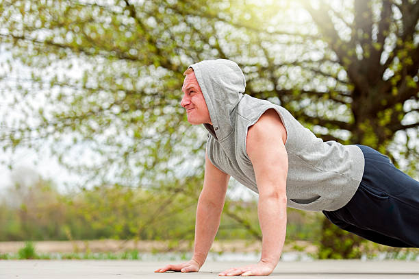 Active man doing push up in park. stock photo