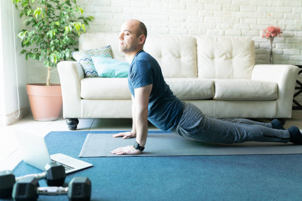 Active man doing yoga at home Portrait of an active man in his 30s doing some yoga and following and online routine on his laptop at home upward facing dog position stock pictures, royalty-free photos & images