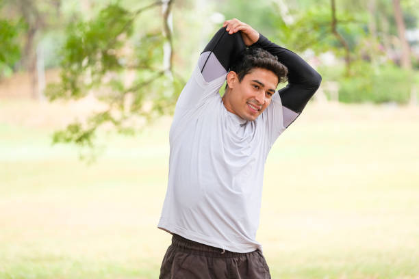 Active man in sportswear stretching one in the park, front view