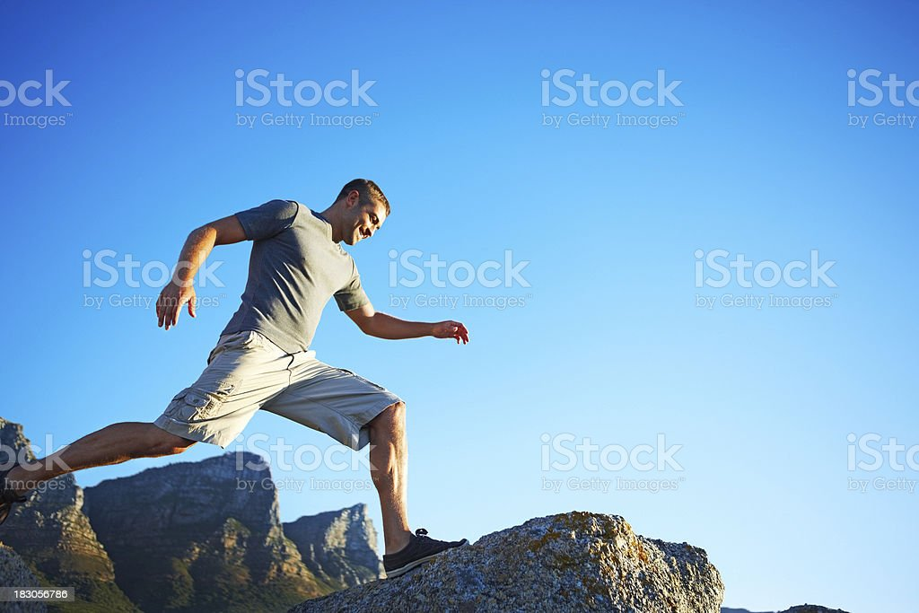 Active man running over rocks against blue sky with copyspace royalty-free stock photo
