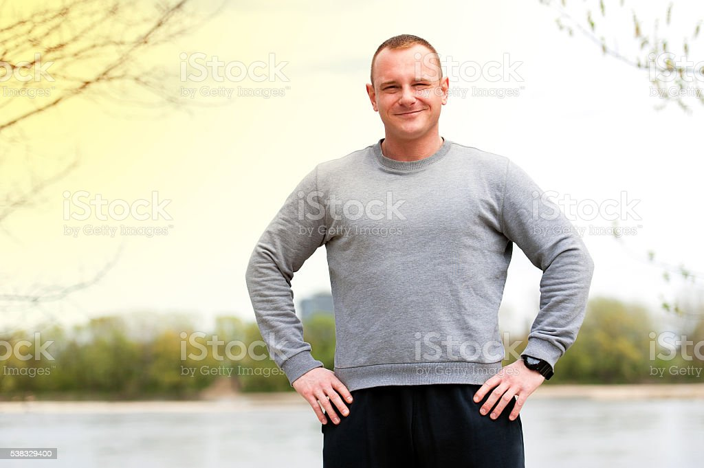 Active man with athletic body and crossed arms, exercise outdoor stock photo