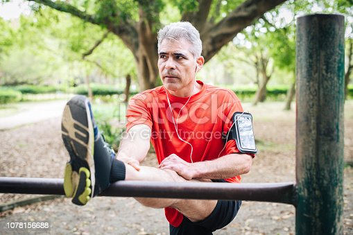Man in his 50s listening to music and stretching leg muscles on bar before running, preparation, flexibility