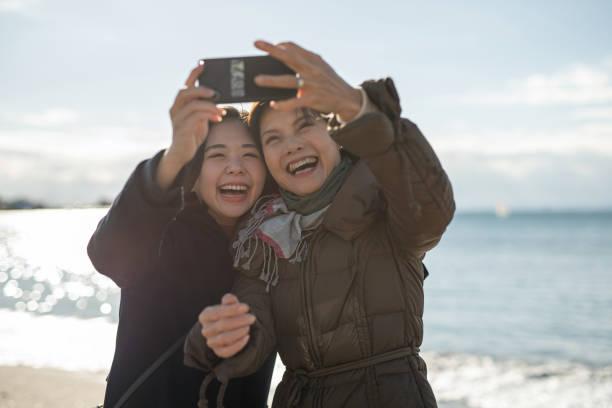 ビーチで彼女の娘と自分撮りを取るアクティブな成熟した女性 - 母娘 笑顔 日本人 ストックフォトと画像