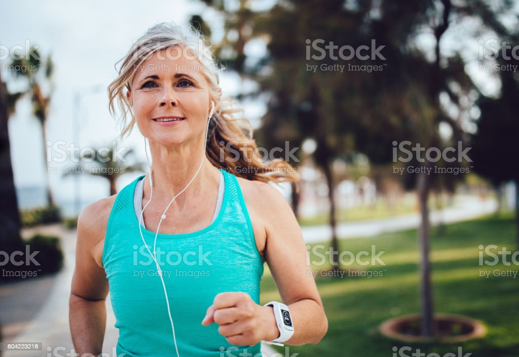 Active mature woman with headphones and smartwatch running in park stock photo