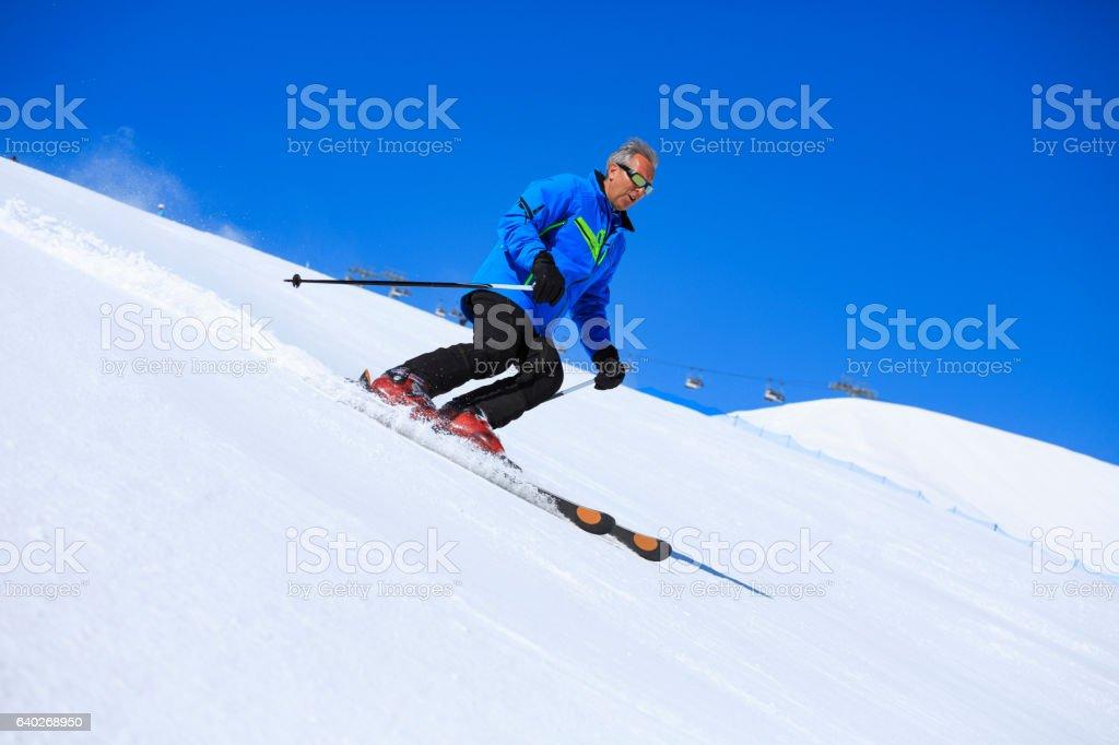 Active mid adult  men snow skier skiing Sunny ski resorts stock photo