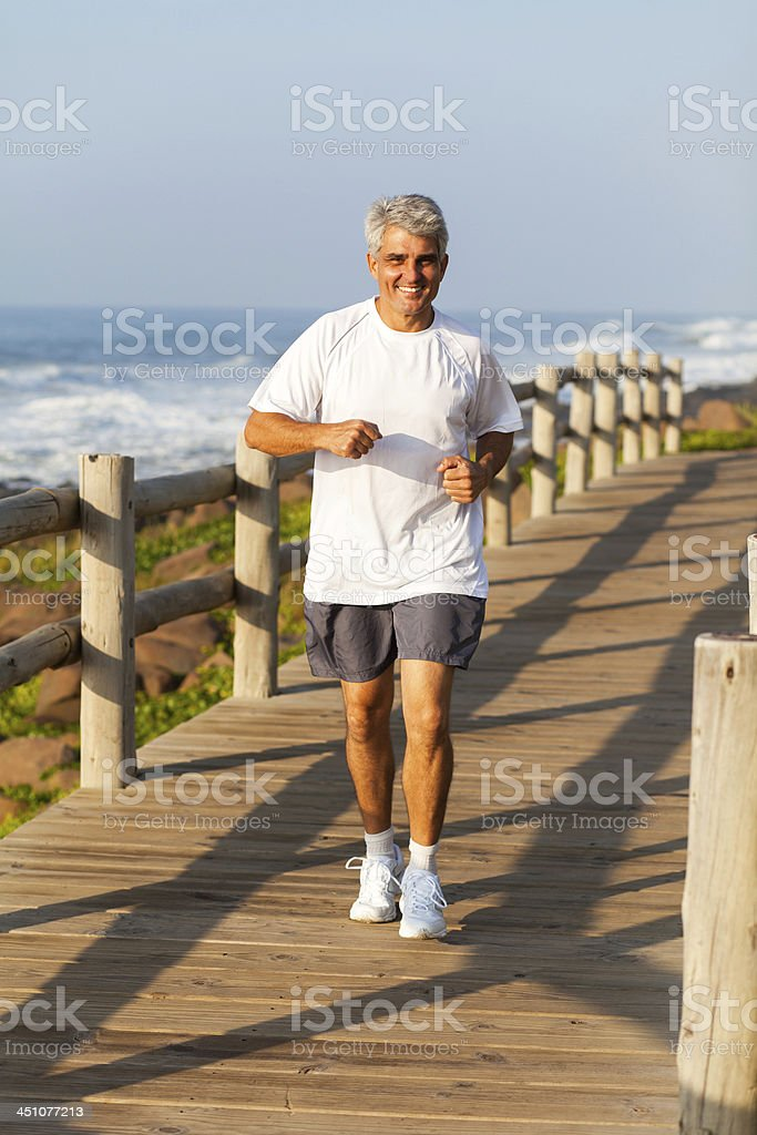 active middle aged man jogging at the beach stock photo