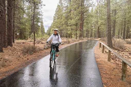 Active mixed race Pacific Islander senior woman smiles while riding her bike along a paved bike path. The environmentally conscious retiree is commuting by bike while vacationing in Oregon. It is a rainy, cool day and the ground is wet from rain. The woman is riding through a wooded rural area.
