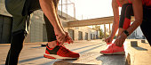 Active morning. Close up photo of two people in sport clothes tying shoelaces before running together outdoors. Fit, fitness, exercise. Healthy lifestyle concept