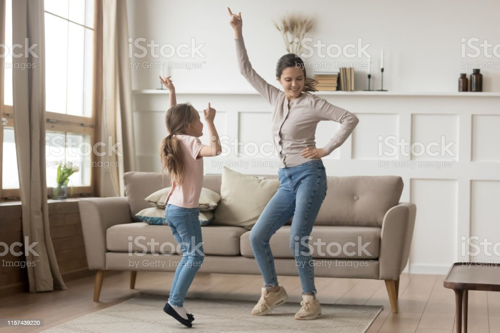Active mother dancing at home with little daughter - Foto stock royalty-free di Adulto