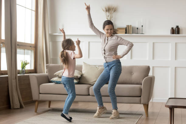 Active mother dancing at home with little daughter Active family young mother dance having fun with little preschool or school age daughter older younger sister listens happy song moving together, leisure activities with kid positive emotions concept dancing stock pictures, royalty-free photos & images