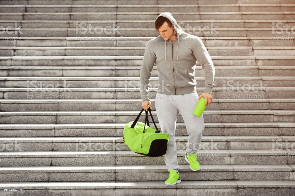 Active muscular sport man holding shaker and sports bag, training outdoors royalty-free stock photo