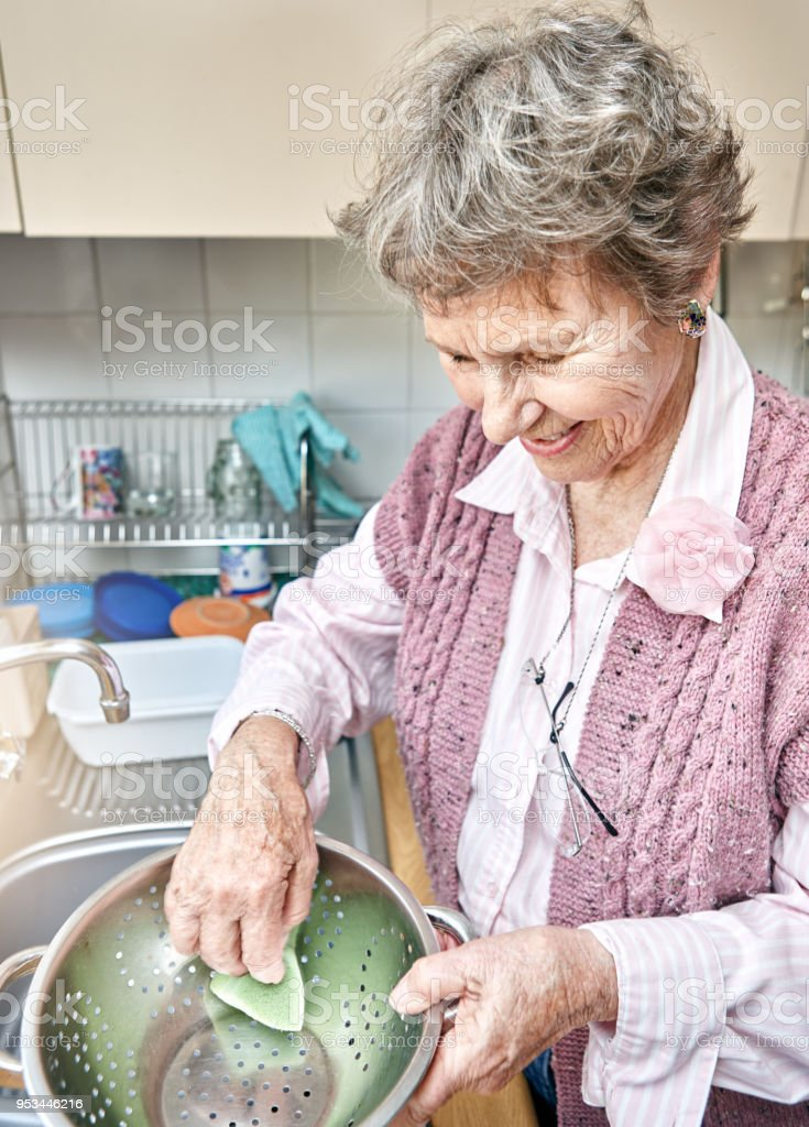 Active Old Woman Smiles Busy With Household Chores Stock Photo