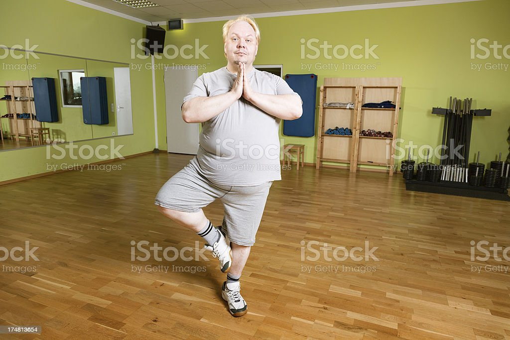 overweight man making syoga exercise in gym, with comcentration
