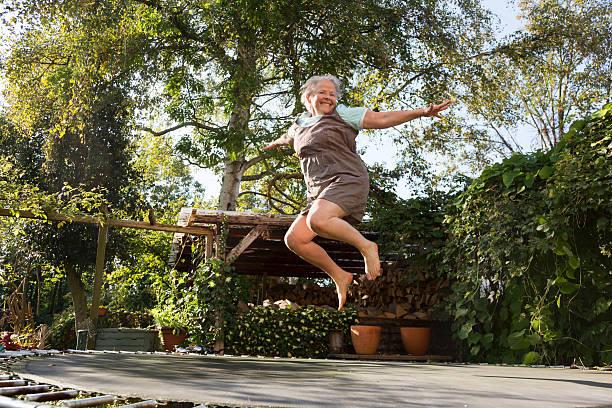 aktive dick senior frau springen auf trampolin - gartentrampolin stock-fotos und bilder