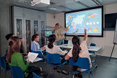 A group of female students are looking at a world strategy map on an interactive screen, one is holding up her hand to ask a question. The classroom indicates, the theme connected with worldwide healthcare.