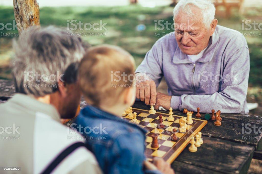 Ativos e aposentados, velhos amigos e tempo livre, dois homens se divertindo e jogando xadrez no parque, passam tempo com o neto - Foto de stock de 4-5 Anos royalty-free