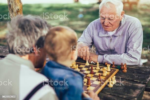 Foto de Ativos E Aposentados Velhos Amigos E Tempo Livre Dois Homens Se Divertindo E Jogando Xadrez No Parque Passam Tempo Com O Neto e mais fotos de stock de 4-5 Anos