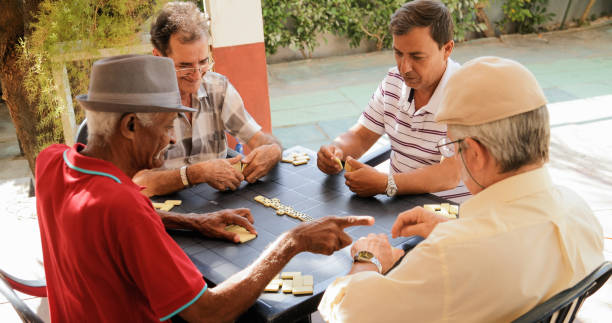 active retirement happy old friends playing domino game - game of life stock photos and pictures