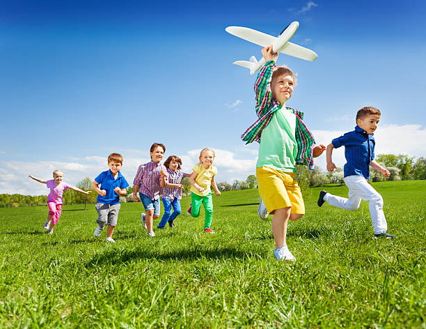 Active running kids with boy holding airplane toy stock photo