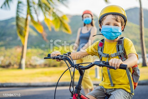 Active school kid boy and his mom in medical mask and safety helmet riding a bike with backpack on sunny day. Happy child biking on way to school. You need to go to school in a mask because of the coronavirus epidemic.