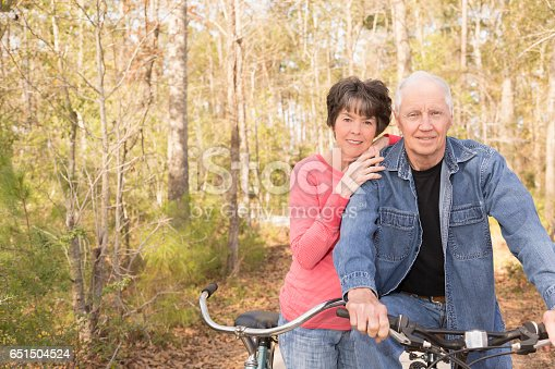 1029243348 istock photo Active senior adult couple biking in park. 651504524
