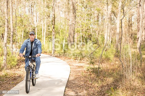 1029243348 istock photo Active senior adult man biking in park. 651512270