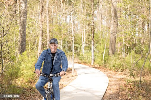 1029243348 istock photo Active senior adult man biking in park. 666082130