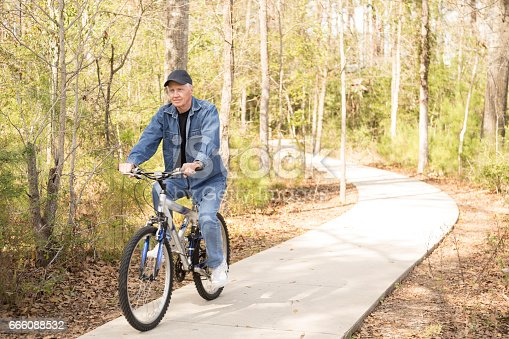 1029243348 istock photo Active senior adult man biking in park. 666088532