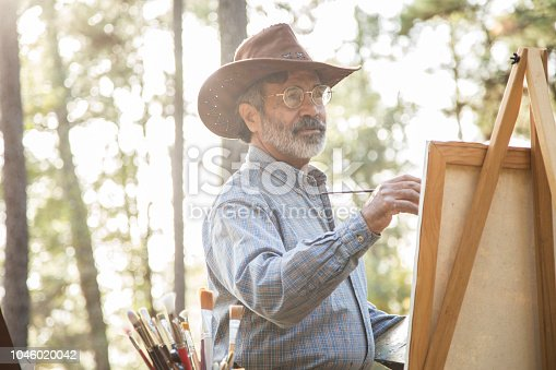 Active senior adult man enjoys art hobby outdoors in public park or forest area.