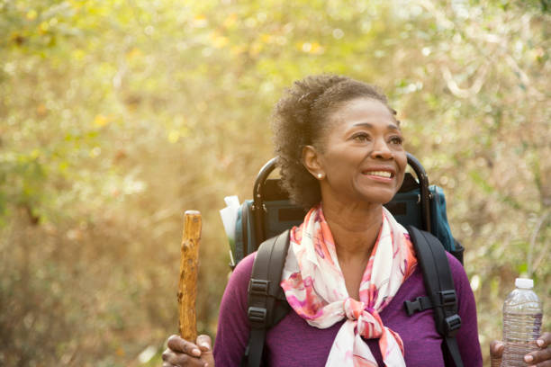 Active senior adult woman hiking in wooded forest area. stock photo