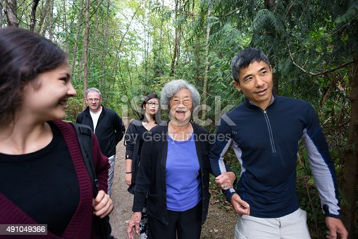 1051098428istockphoto Active Senior Asian Woman Walking in Wooded Trail with Family 491049366